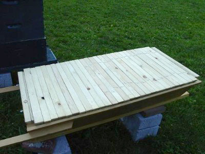 Here is a picture with the cover off. You can now see the top bars, which are the only support point that the bees use to build their natural comb. Each top-bar is 1-3/8 inches wide, except the front and back, which are 1-9/16 inches wide to accomodate a bee space against the front and back walls of the hive. - David Tromp